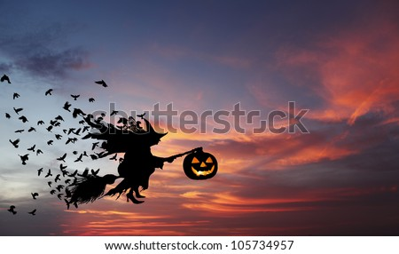 Silhouette of a witch flying on a broomstick carrying a sinister pumpkin lantern with flocks of crow following her during an eerie surreal evening, for Halloween concept. - stock photo