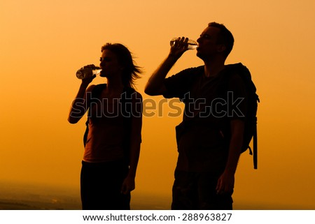 Silhouette of a woman and man with backpack drinking water.Refreshment for hikers - stock photo