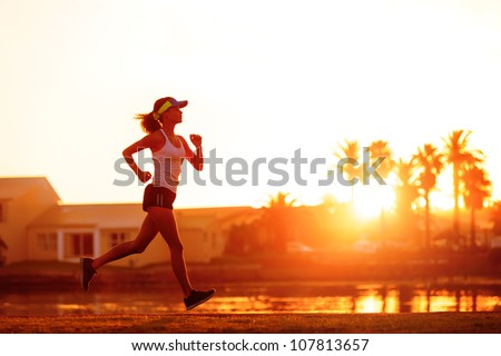 silhouette of a woman athlete running at sunset or sunrise. fitness training of marathon runner. - stock photo