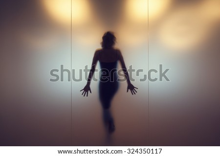 Silhouette of a woman behind a glass wall. - stock photo