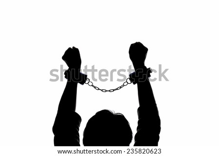 Silhouette of a woman in handcuffs holding arms and fists aloft - stock photo
