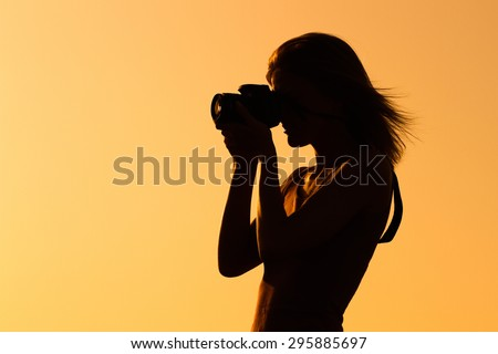 Silhouette of a woman photographing. Woman photographing - stock photo