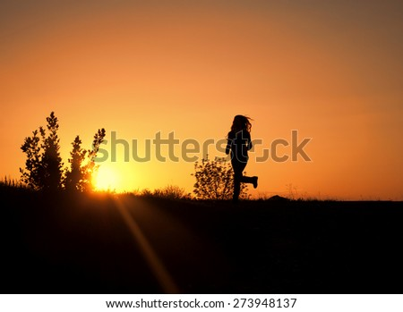 Silhouette of a woman running - stock photo