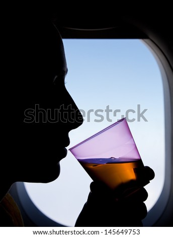 Silhouette of a woman sitting next to the window in the Airplane, drinking a beverage. - stock photo