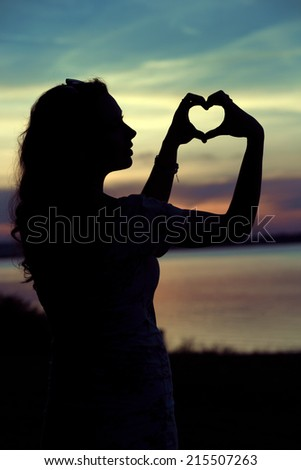 Silhouette of a woman standing in front of the sunset - stock photo