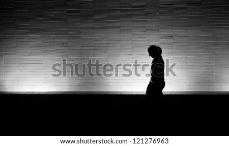 Silhouette of a woman walking at night in the city - stock photo
