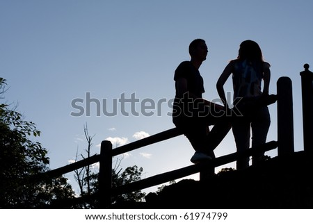 Silhouette of a young couple hanging out together outdoors by an old country fence during the early evening hours. - stock photo