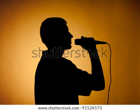 Silhouette of a young man in orange, darkened at the edges. - stock photo