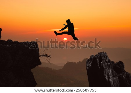 silhouette of a young man jumping off a step up cliff in the direction of sunrise the morning sun light sky outdoor on the mountain. - stock photo
