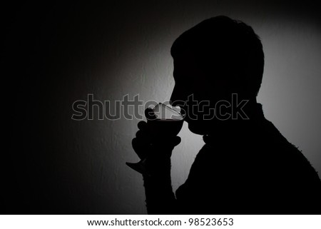 silhouette of a young man with a glass of red wine on a gray background - stock photo