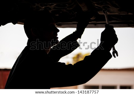 Silhouette of a young mechanic working an a suspended car at an auto shop - stock photo
