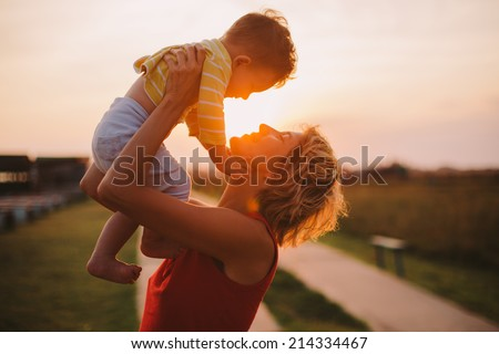 Silhouette of a young mother and her little son at sunset - stock photo