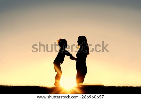 Silhouette of a young mother lovingly holding hands with her happy little child outside in front of a sunset in the sky. - stock photo