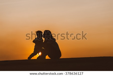 Silhouette of a young mother lovingly kissing her little child o - stock photo
