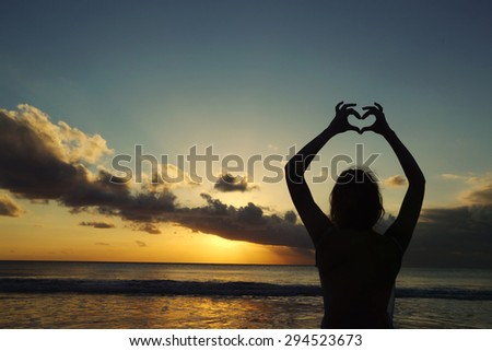 Silhouette of a young woman creating the shape of a heart with her hands against sunset background  - stock photo