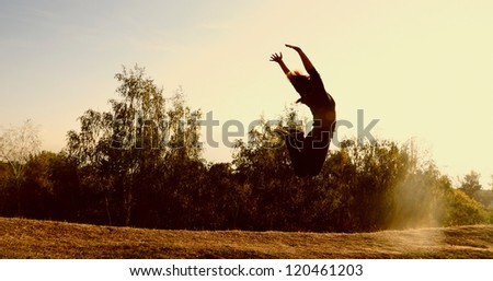 Silhouette of a young woman jumping - stock photo
