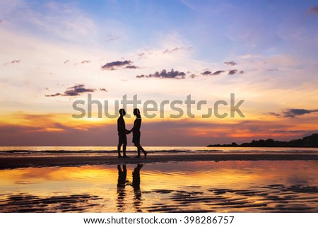 silhouette of affectionate couple on the beach at sunset, love concept, man and woman, beautiful background - stock photo