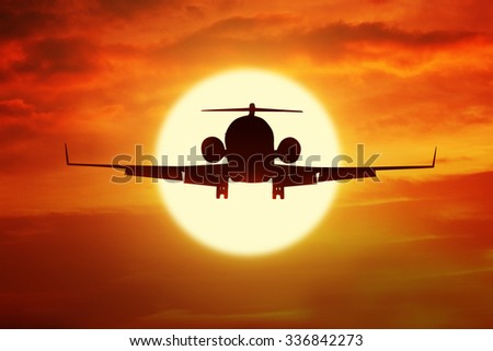 Silhouette of aircraft flying on the sky with orange color at sunset time - stock photo