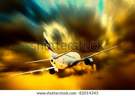 Silhouette of airplane on sunset sky - stock photo