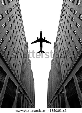 Silhouette of an airplane flying pass between two highrise building in a city. - stock photo
