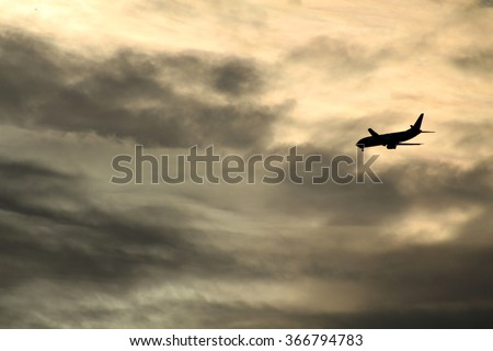 Silhouette of an airplane in the sky against some dramatic clouds. - stock photo