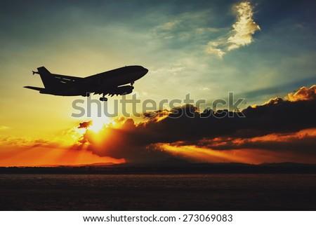 Silhouette of an airplane landing. Beautiful sunset evening sky. - stock photo