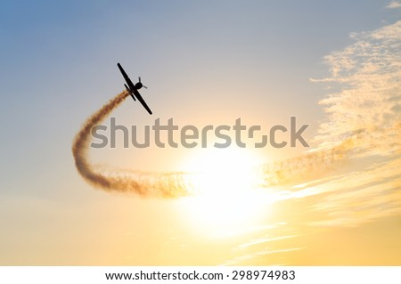 Silhouette of an airplane performing acrobatic flight at sundown. Trace of Smoke behind it - stock photo