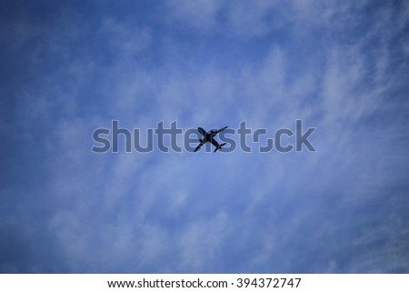 Silhouette of an airplane taking off into a surreal colorful evening sky - stock photo
