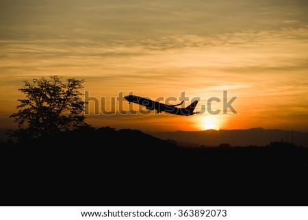 Silhouette of an airplane taking off, Sunrise in the morning sky. - stock photo