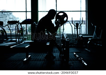 silhouette of an athletic man working out at gym. Fitness bodybuilder training in the gym - stock photo