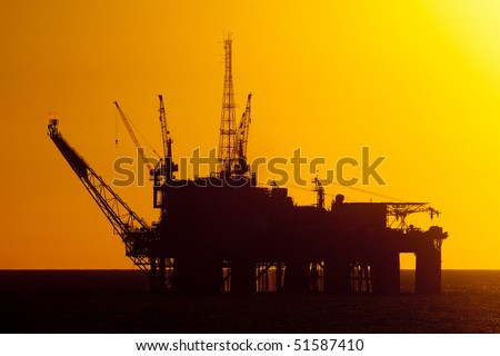 silhouette of an offshore oil rig - stock photo