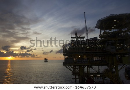 Silhouette of an offshore oil rig at sunset - stock photo
