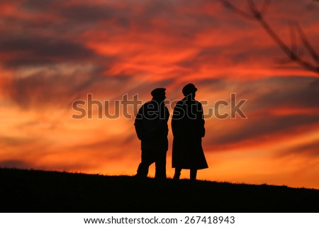 Silhouette of an old couple walking at sunset - stock photo