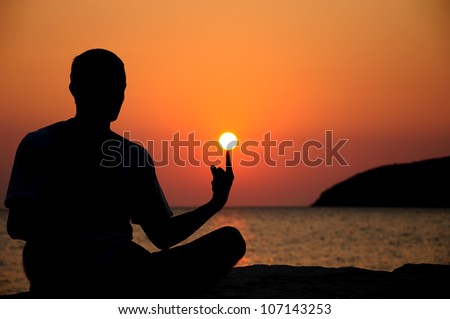 silhouette of an young man on sunrise - stock photo