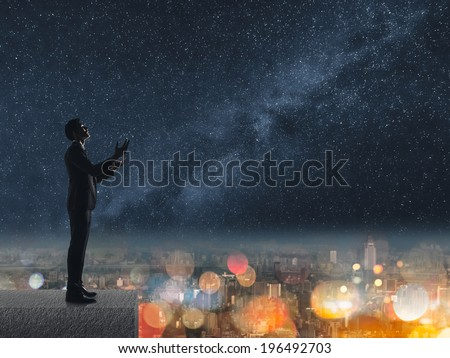 Silhouette of Asian businessman standing and praying at the roof under stars night in city. - stock photo