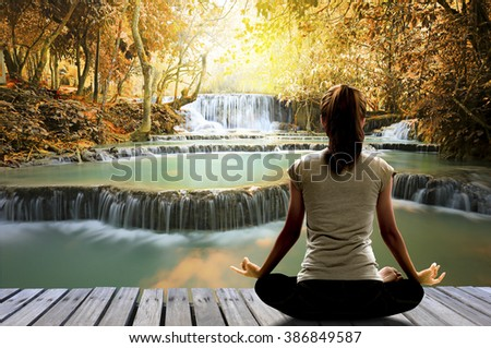 Silhouette of Asian woman yoga on the wooden bridge over waterfall in the autumn forest at the sunrise in the morning. Image create for business, healthcare, sport and lifestyle of people., - stock photo