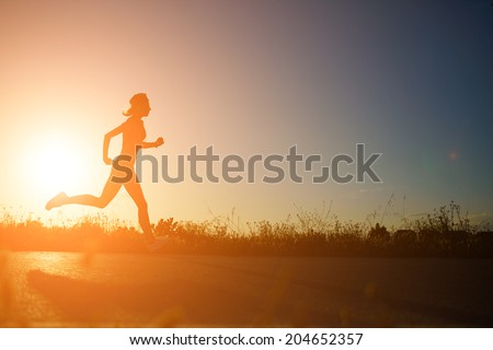 Silhouette of athletic girl running down the beautiful road at amazing orange sunset, female runner with muscular body at evening run,  fitness and healthy lifestyle concept - stock photo