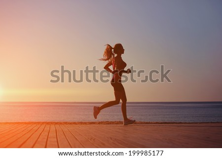 Silhouette of attractive female runner with a beautiful strong figure running along the beach on the wooden pier, sea background - stock photo