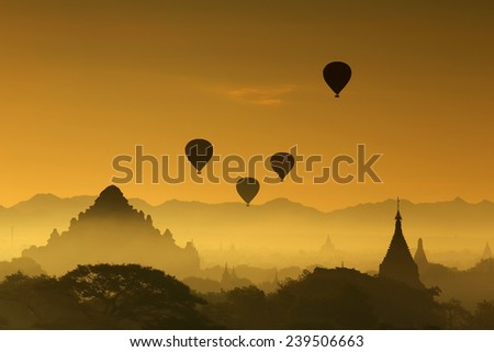 Silhouette of balloons over the pagoda temples with fog sunrise of Bagan in Myanmar - stock photo