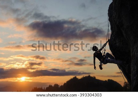 Silhouette of beautiful athletic woman climbing steep rock wall against amazing sunset scene in the mountains. Girl is hanging on one hand and looking up. - stock photo