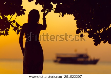 silhouette of beautiful young woman against beautiful sunset and boat - stock photo