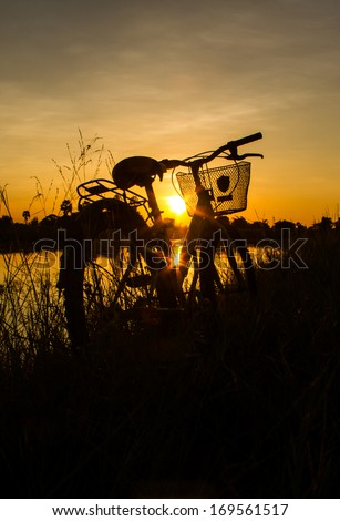 Silhouette of bicycle beside the pond in the evening. - stock photo