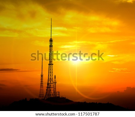 Silhouette of big communication antenna in a woderful orange sunset - stock photo