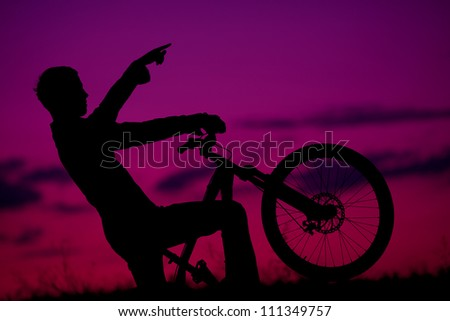 silhouette of boy cyclist in motion on the background of beautiful sunset (dawn) showing something ahead - stock photo