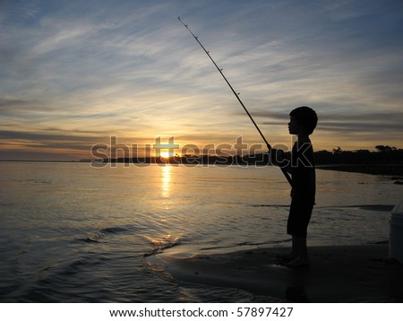 Silhouette of boy fishing - stock photo