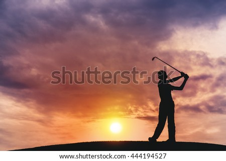 silhouette of boy golfer with golf club at sunset - stock photo