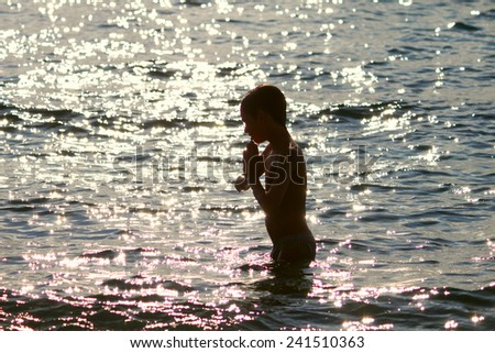 Silhouette of boy jumping in sea at sunset - stock photo
