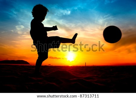 silhouette of boy kick the ball at sunset - stock photo