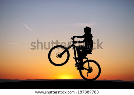 silhouette of boy riding his mountain-bike in sunset  - stock photo
