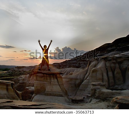 Silhouette of boy standing on rocks with sunflare - stock photo